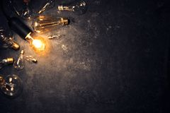 Free Vintage Old Light Bulb Glowing On Rough Dark Background Surrounded By Burnt Out Bulbs. Idea, Creativity Concept Royalty Free Stock Photography - 164472987
