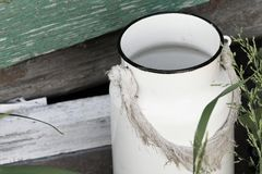 Vintage old milk can in the village. An old white enamelled can of white color with a rag tied in place of the handle stands in the grass near the wall of an stock photos