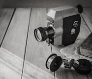 Vintage old movie camera and film reels on a wooden table, old book, clothl. Retro photo. Copy space. royalty free stock images