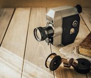 Vintage old movie camera on a wooden table, old book, clothl. Retro photo. Copy space. royalty free stock image