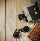 Vintage old movie camera on a wooden table, old book, clothl. Retro photo. Copy space. Top view. stock photography