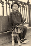 Vintage old photo of a little girl and his dog. Little girl sitting on the road with a dog and a suitcase Stock Photo