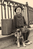 Vintage old photo of a little girl and his dog. Little girl sitting on the road with a dog and a suitcase Royalty Free Stock Image