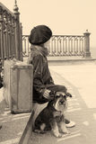 Vintage old photo of a little girl and his dog. Little girl sitting on the road with a dog and a suitcase Royalty Free Stock Photos