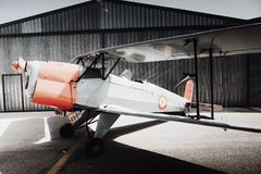 Vintage old plane in front of the hangar. Wings side view. Classic vintage airplane at the hangar Stock Photos