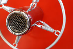 Vintage old round studio voice microphone over red. Vintage retro style old metal professional studio vocal voice and music recording microphone suspended with Royalty Free Stock Photos