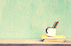 Vintage old school. Old cup with books and crayons vintage concept Royalty Free Stock Photo