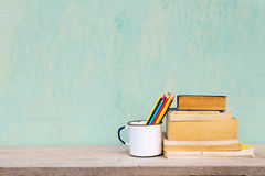 Vintage old school. Old cup with books and crayons vintage concept Stock Photo