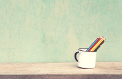 Vintage old school. Old cup with books and crayons vintage concept Stock Photography