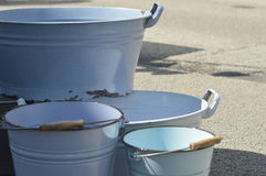 Vintage. Old steel buckets in blue contrasting with grey color of the asphalt Royalty Free Stock Images