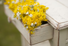 Vintage old table and wild flowers. Vintage old table and wild yellow  flowers Stock Image