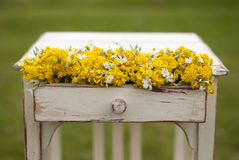 Vintage old table and wild flowers. Vintage old table and wild yellow  flowers Royalty Free Stock Image