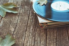 Vintage old vinyl records on wooden autumn background, selective focus decorated with few leaves. Music, fashion, texture,. Art concepts. pop culture and Stock Photos