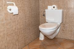 Vintage old white toilet bowl with brown tiles Stock Image