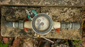 Vintage Old White Water Meter on Dirty Concrete/ Stone in the Ga royalty free stock image