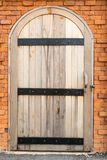 Vintage old wooden door on a red brick wall Stock Photo