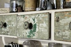 Vintage old wooden drawer in cupboard in workshop. Closeup on closed drawer. Green lacquer Stock Photos