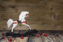Vintage - old wooden rocking horse on a wooden old board for a c. Vintage, old wooden rocking horse on a wooden old board for a christmas card with red balls Royalty Free Stock Photography