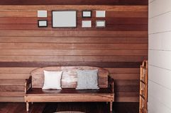 Vintage old wooden wall living room with wooden couch, pillows,. Asian style vintage old wooden wall living room with wooden couch, pillows, lamp and photo frame Stock Photo