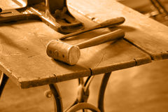 Vintage Old Worktable. View of a mallet on antique worktable. Tinted in sepia for effect Royalty Free Stock Photos