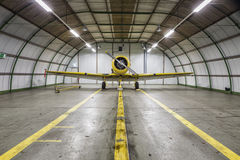 Vintage old yellow war plane inside of a empty hangar royalty free stock photography