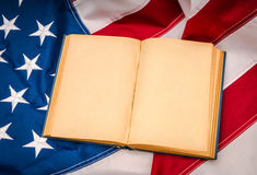 Vintage open book on American flag. Stock Image