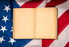 .Vintage open book on American flag Royalty Free Stock Images