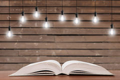 Vintage open book on the desk and light bulbs on the background Royalty Free Stock Photo