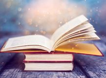 Vintage open book. Open book with magic lights. Concept of wisdom, religion, reading, imagination, winter holidays stock photos