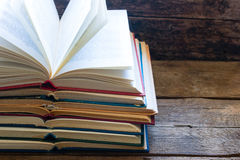 Vintage opened books on a wooden background. And space for text stock image