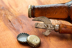 Vintage opener and beer. Over wooden surface Stock Photo