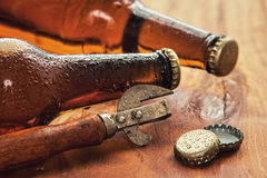 Vintage opener and beer. Over wooden surface Stock Image