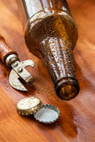 Vintage opener and beer. Over wooden surface Royalty Free Stock Photography