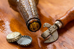 Vintage opener and beer. Over wooden surface Royalty Free Stock Image