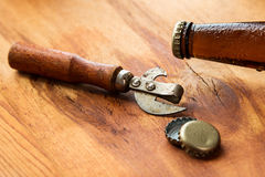 Vintage opener and beer on the table. Vintage opener and beer over wooden surface Stock Image