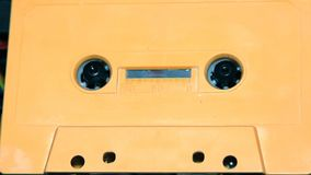 Orange audio cassette tape with a blank label