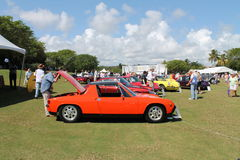 Vintage orange Porche at boca raton resort. Man looking his car's engine. mid-engined Porsche on display in a lineup among other Porshce sportscar at the Porsche Royalty Free Stock Image