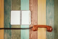 Vintage orange telephone receiver and notebook Stock Image
