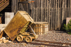 Vintage Ore Cart on Tracks Outside Wood Building. Historic Ore Cart On Track Dumping Load From Mining Operations stock photography