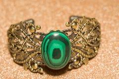 Bronze Bracelet with Malachite. Vintage ornamental bronze bracelet with big green stone malachite imitation royalty free stock photos