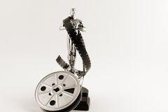 Vintage Oscar statue with movie reel desaturated. Academy Award Oscar statue in silver with vintage movie film reel desaturated with sepia tones and copy space royalty free stock photos