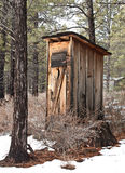 Vintage Outhouse in Forest Snow. A vintage outhouse sits in the forest in a winter snow royalty free stock photos