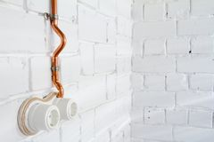 A vintage outlet and electrical wiring in a copper tube. Retro socket made of white ceramic with open electrical wiring. Against the background of a white brick Stock Photo