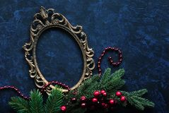 Vintage oval frame and christmas decor. Vintage metal oval frame on a dark background with Christmas decoration Royalty Free Stock Photography