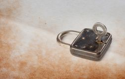 Vintage padlock with key in hole, aged textured paper background. copy space.  Stock Images