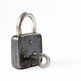 Vintage padlock with key in hole. hanging lock close-up. texture and detailed. white background. Royalty Free Stock Photography