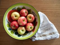 Vintage Painted Tin Bowl with Apples and Dish Towel from Above stock images