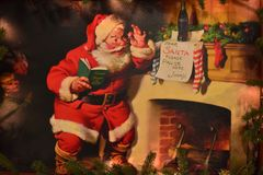 Vintage painting of Santa Claus by fireplace in International Drive area.