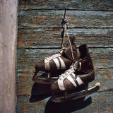 Vintage pair of mens  ice skates hanging on a wall Stock Photos