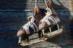 Vintage pair of mens  ice skates hanging on a wooden wall with c Royalty Free Stock Photography